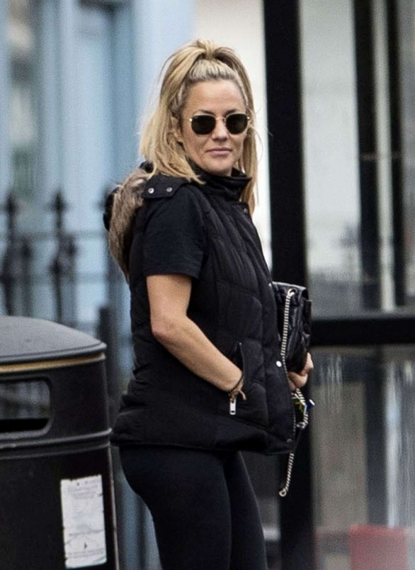 Caroline Flack looks in high spirits during a smitten stroll with beau Lewis Burton after her bitter ex Andrew Brady slams their 'toxic' romance and covers tattoo of her initials