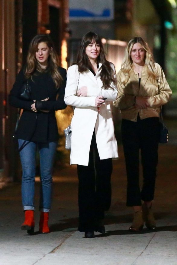 Dakota Johnson has a ladies night out bundled up in glamorous white coat with flowing black trousers