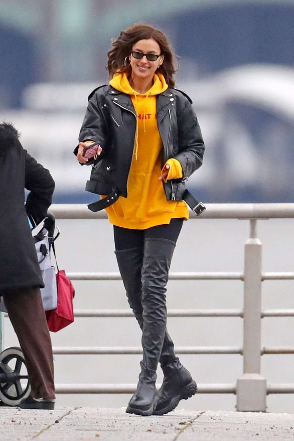 Irina Shayk dances in the street in thigh-high leather boots and a yellow hoodie as ex Bradley Cooper heads out with their daughter Lea, two