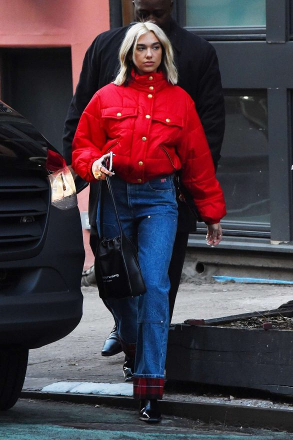 Dua Lipa stands out in contrasting colors as she wears red puffer jacket and blue jeans in New York