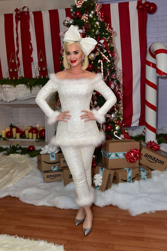 Katy Perry wears white as she sits on Santa's lap while hosting a holiday party for The Boys And Girls Club in Los Angeles