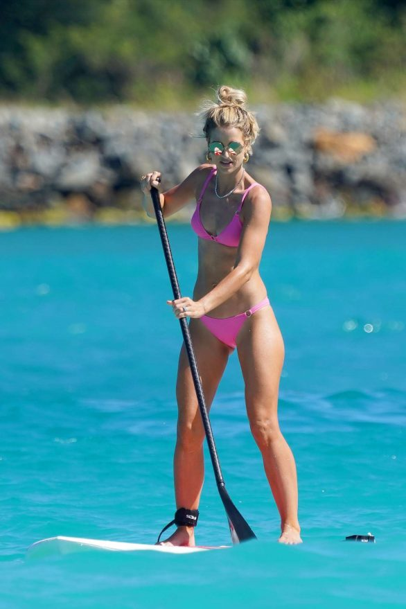 Vogue Williams showcases her honed abs in a pink bikini as she larks around with husband Spencer Matthews on paddle boards during St. Barts getaway