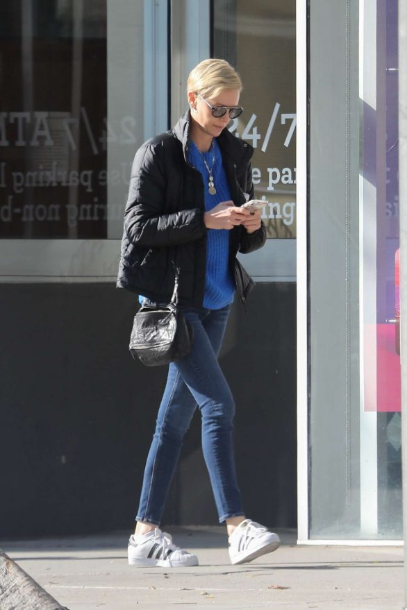 Charlize Theron displays lithe figure in blue sweater and skinny jeans as she runs errands solo in Beverly Hills