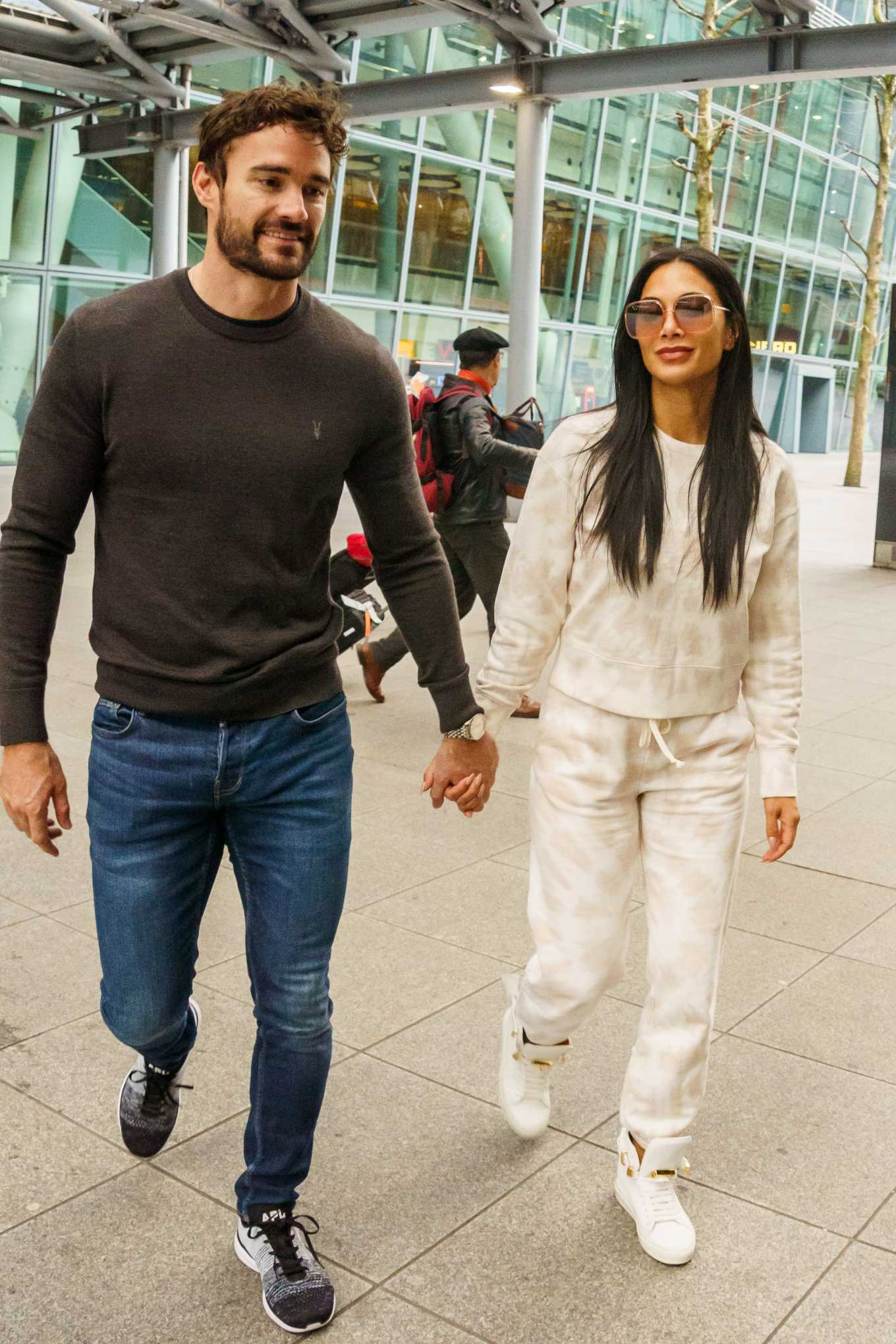 Nicole Scherzinger and boyfriend Thom Evans put on a loved up display as they arrive hand in hand at Heathrow after Los Angeles break